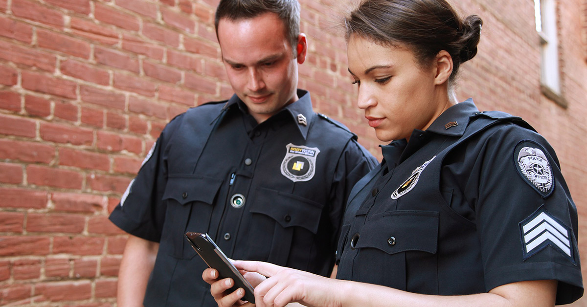 A female uniformed police officer holds a smart phone pointing to the screen while a male uniformed police officer looks on with interest.